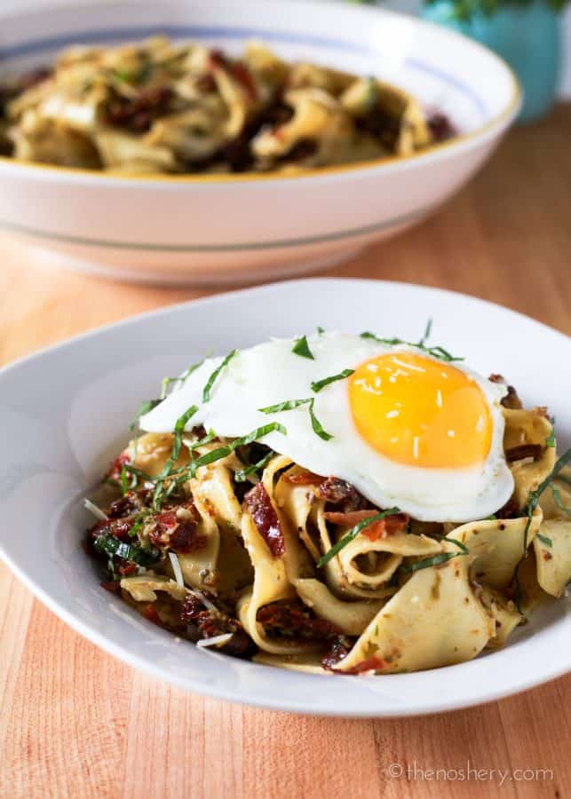 Broad pappardelle pasta noodles toss in a briny and salty olive tapenade with sweet sun-dried tomatoes and crispy prosciutto. Topped with a runny fried egg.