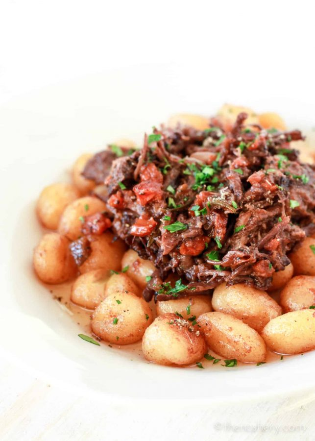 Braised Beef in Red Wine pilled over pan fried gnocchi potato dumplings. | The Noshery