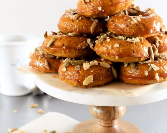 Pumpkin Spiced Donuts with Bourbon Caramel Glaze | A soft and nutty donut packed with pumpkin flavor. But wait, there's more. I dipped them in a gooey bourbon caramel glaze! | TheNoshery.com