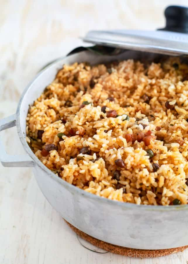 Arroz con Gandules (Puerto Rican Style Rice and Pigeon Peas) | Large pot of orange colored rice with small dark beans and bacon.