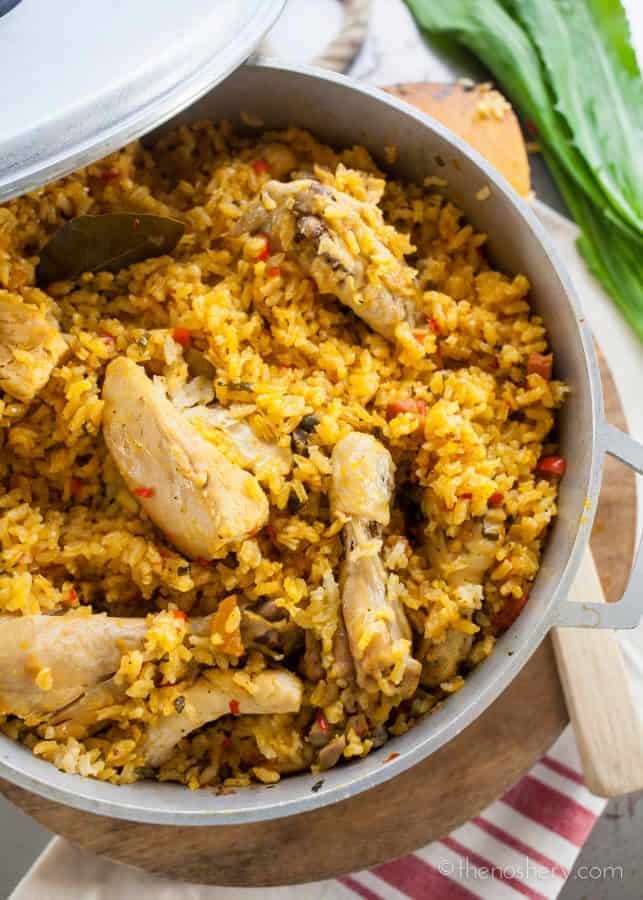 Arroz con Pollo - Overhead shot of chicken and yellow rice in a large pot.