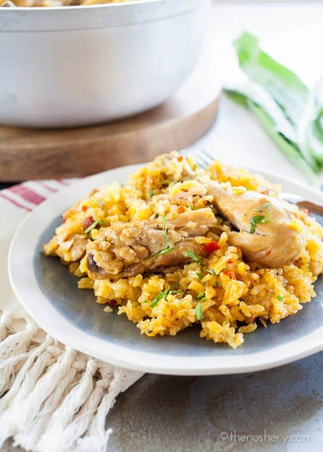 Arroz con Pollo - Chicken and yellow rice on a plate.