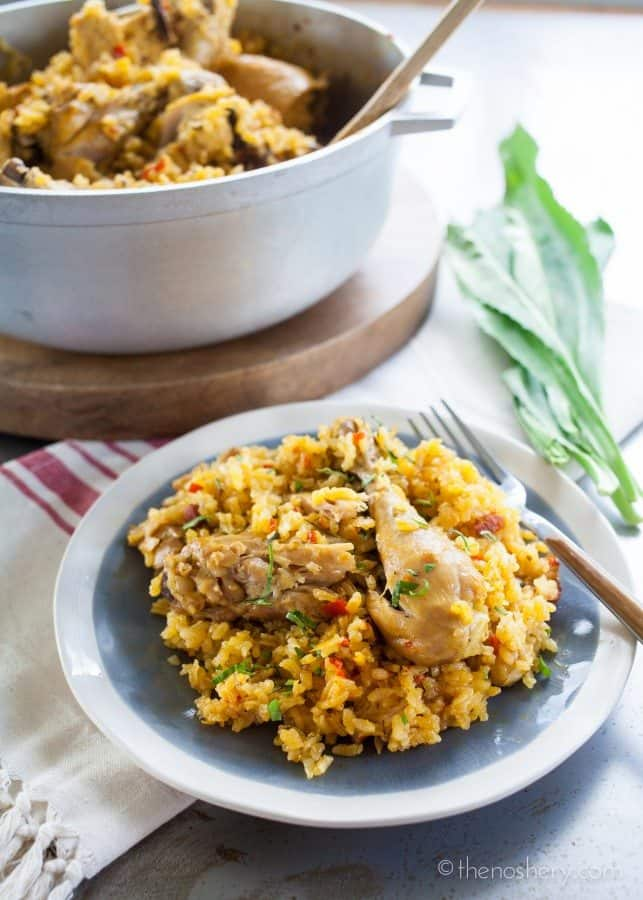 Arroz con Pollo | Side view of chicken and yellow rice on a plate with a large pot in the background.