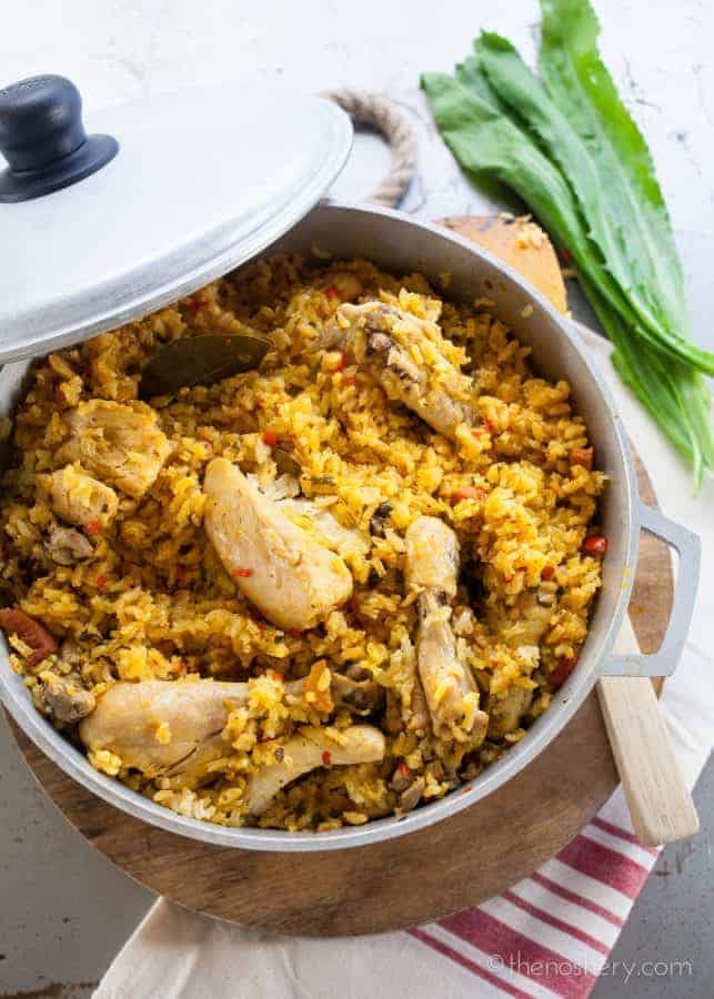 Arroz con Pollo (Chicken and Rice) - Overhead view of chicken and yellow rice in a large pot.