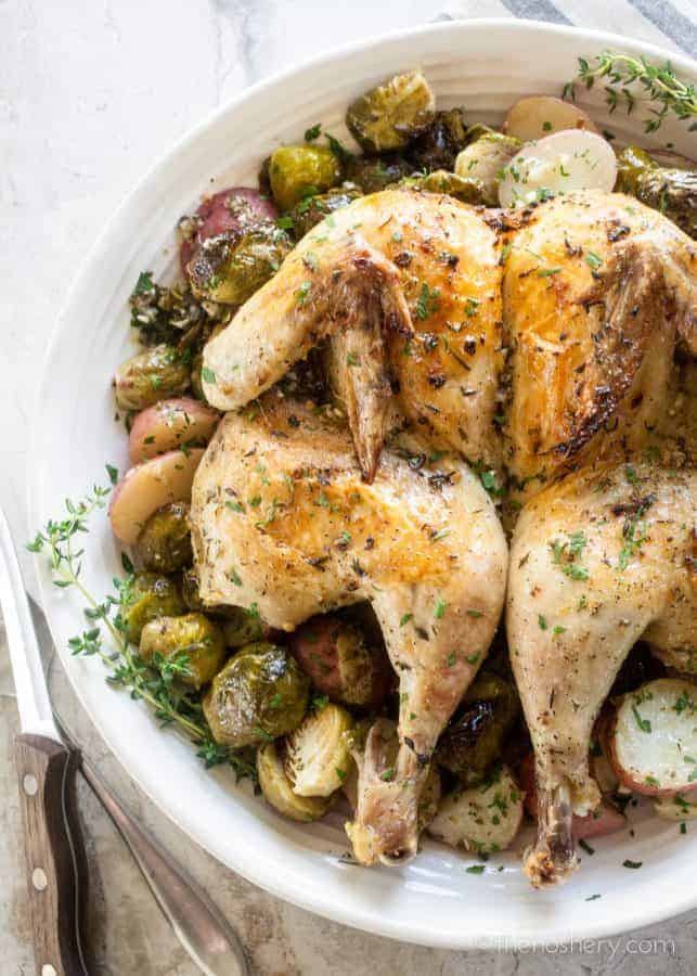 Lemon Garlic Spatchcock Chicken Dinner | Platter of whole spatchcock chicken on a bed of roasted Brussels sprouts and potatoes. | The Noshery