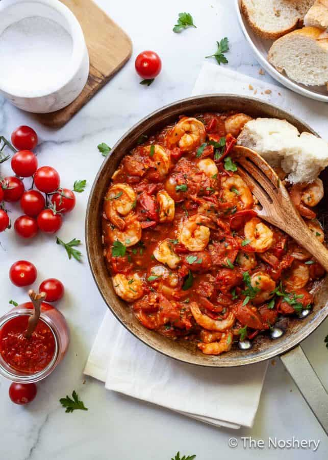 Easy Shrimp Harissa and Tomato Skillet | If you like food that is saucy, spicy and takes 20 minutes to make you will love this skillet. Large shrimp are sautéd in a harissa spiced tomato sauce and served with crusty bread. This harissa and tomato shrimp is also great to toss in pasta or served over polenta. | The Noshery
