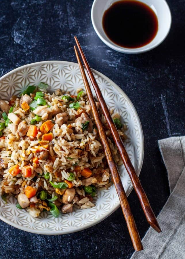 Overhead shot of chicken fried rice with chopsticks resting on bowl| The Noshery