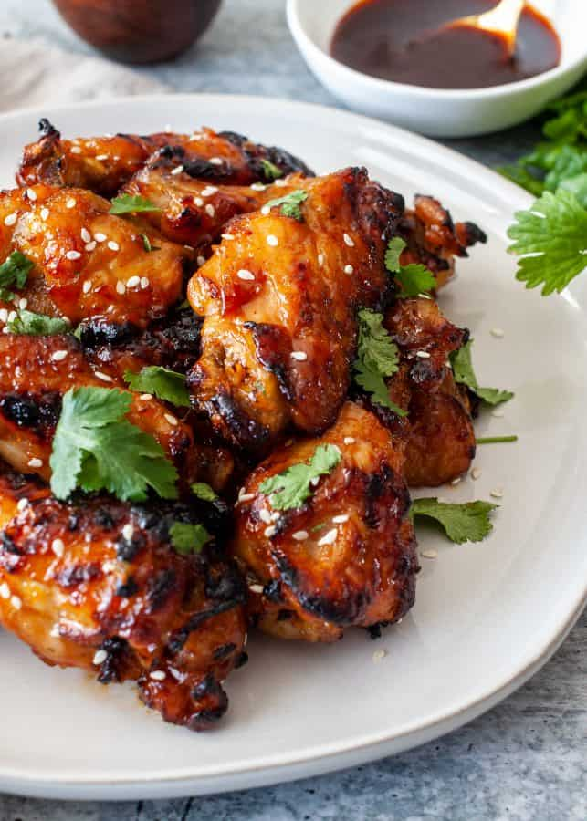Instant Pot Sticky Gochujang Chicken Wings | Overhead shot of glazed chicken wings on a place with sauce in background. Wings are garnished with cilantro and sesame seeds.